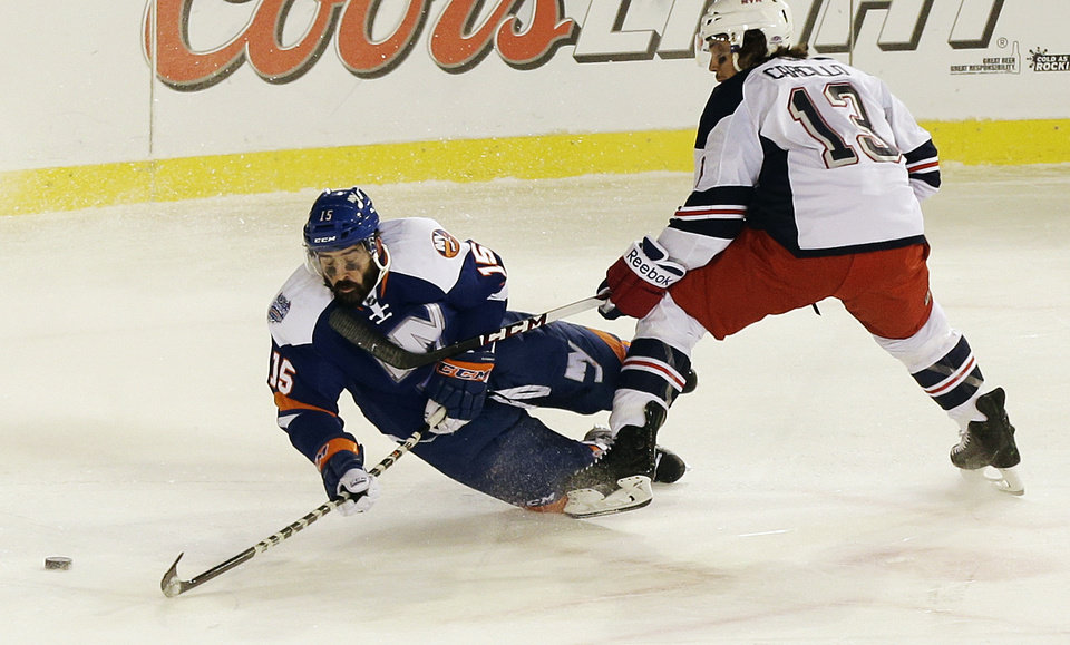 Photo - New York Islanders' Cal Clutterbuck (15) and New York Rangers' Daniel Carcillo (13) fight for control of the puck during the second period of an outdoor NHL hockey game  Wednesday, Jan. 29, 2014, at Yankee Stadium in New York. (AP Photo/Frank Franklin II)