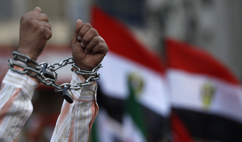 A protester shows his chained hands during a demonstration against a constitution drafted by Islamist supporters of President Mohammed Morsi in Tahrir square in Cairo, Egypt, Friday, Dec. 14, 2012. Opposing sides in Egypt's political crisis were staging rival rallies on Friday, the final day before voting starts on a contentious draft constitution that has plunged the country into turmoil and deeply divided the nation.(AP Photo/Petr David Josek) ORG XMIT: PJO122