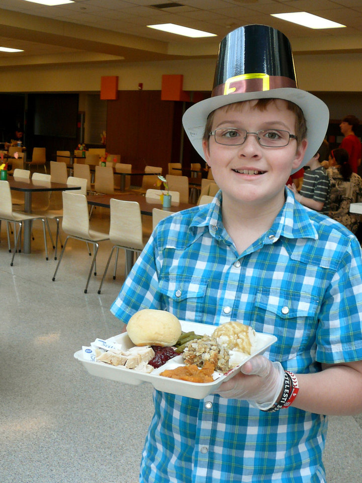 Volunteer Brenton Fairchild, 11, carries a meal to a table at Norman's Community Thanksgiving Dinner. PHOTO BY CONNIE HEFNER, FOR THE OKLAHOMAN <strong>Connie Hefner</strong>