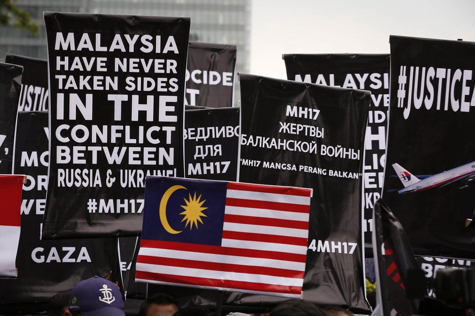 Photo - Banners are held up by protesters during a protest in front of Ukraine embassy in Kuala Lumpur, Malaysia, Tuesday, July 22, 2014. Protesters marched on the Russian embassy and Ukraine embassy in Kuala Lumpur on Tuesday, waving placards and demanding justice for the victims of the Malaysia Airlines flight that was shot down over Ukraine last week. (AP Photo/Vincent Thian)