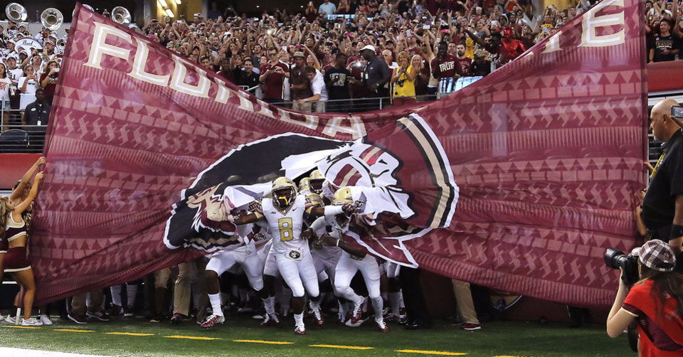 Photo - Florida State makes their way onto the field for the start of the college football game between Oklahoma State University (OSU) and Florida State University (FSU) at the AdvoCare Cowboys Classic at AT&T Stadium in Arlington, Texas on Saturday, Aug. 30, 2014. Photo by Chris Landsberger, The Oklahoman