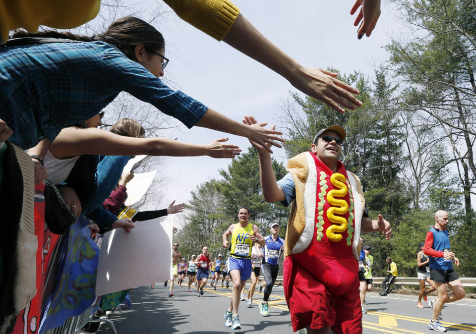 Photo - FILE -- In this April 15, 2013 file photo, a man dressed as a hot dog runs through Wellesley, Mass., during the 117th running of the Boston Marathon. Security will be tightened for the 2014 Boston Marathon after twin explosions killed three people and injured more than 260 near the finish line of the race in 2013. New rules include a limit on the size of water bottles, restrictions on bulky costumes, and nothing covering the face.(AP Photo/Michael Dwyer, File)