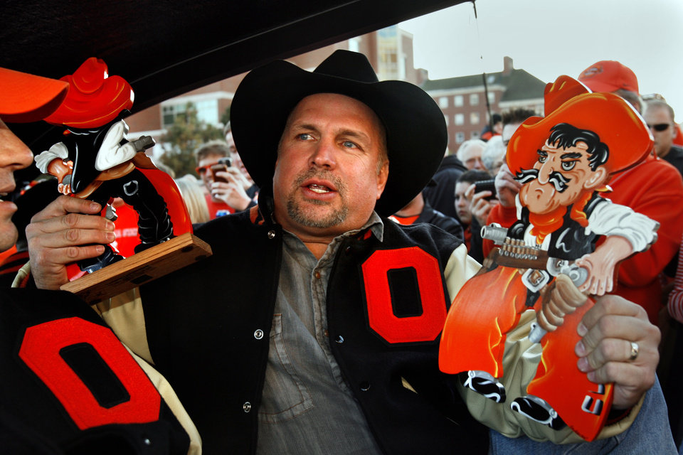 Photo - Country music star Garth Brooks accepts gifts from the crowd as he rides to a press conference following his
