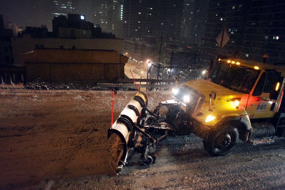 Photo - A plow drives across the Brooklyn Bridge during a winter storm in New York, late Thursday, Jan. 2, 2014. The storm is expected to bring snow, stiff winds and punishing cold into the Northeast. (AP Photo/Karly Domb Sadof)