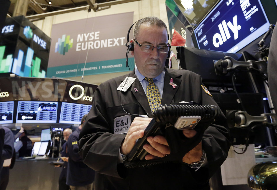 Photo - Trader John Yaccarine works on the floor of the New York Stock Exchange Thursday, April 10, 2014.  U.S. stock indexes are slipping lower in early trading Thursday as investors pick over a mixed batch of corporate earnings reports. (AP Photo/Richard Drew)