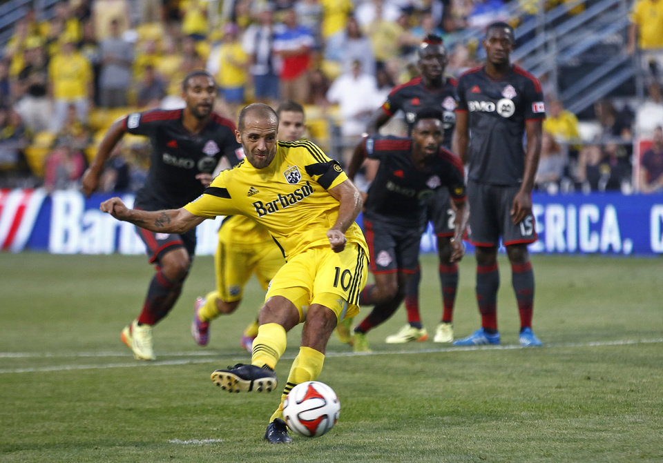 Photo - Columbus Crew forward Federico Higuain (10) scores on a penalty kick in the first half of an MLS soccer game against Toronto FC on Saturday, Aug. 9, 2014, in Columbus, Ohio. (AP Photo/The Columbus Dispatch, Eamon Queeney)