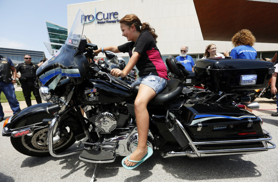 Photo -  Katie McGann, 11, has been fascinated with Harley-Davidson motorcycles for years. On Wednesday, the girl from England celebrated nearing the end of her cancer treatment in Oklahoma City with a motor- cycle sendoff.  She returns home next week. At left, Katie sits on an Oklahoma County Sheriff's Office motorcycle.  [Photo by Nate Billings, The Oklahoman]