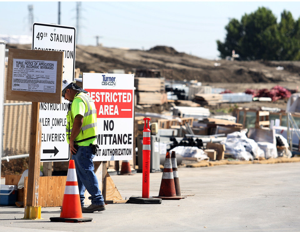 Photo - A security guard walks by a construction entrance at the Forty-Niners' new stadium Monday, Oct. 14, 2013, in Santa Clara, Calif., where a second worker has been killed in an accident in less than four months.  A delivery truck driver was crushed early Monday by a bundle of rebar being unloaded from his truck, officials at the scene said. (AP Photo/Mathew Sumner)