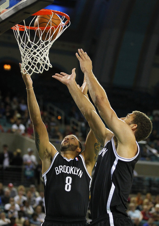 Brooklyn Nets\' Deron Williams (8) and Brook Lopez (11) attempt to grab a rebound against the Philadelphia 76ers in the first half during a preseason NBA basketball game, Saturday, Oct. 13, 2012, in Atlantic City, N.J. (AP Photo/Rich Schultz)