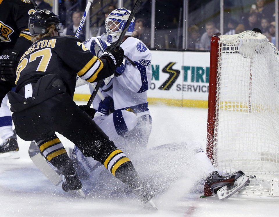 Photo - Tampa Bay Lightning center Steven Stamkos, below, bangs into the goalpost defending against Boston Bruins defenseman Dougie Hamilton (27) as goalie Anders Lindback defends the net during the second period of an NHL hockey game in Boston Monday, Nov. 11, 2013. Stamkos was taken off the ice on a stretcher after the play. (AP Photo/Elise Amendola)