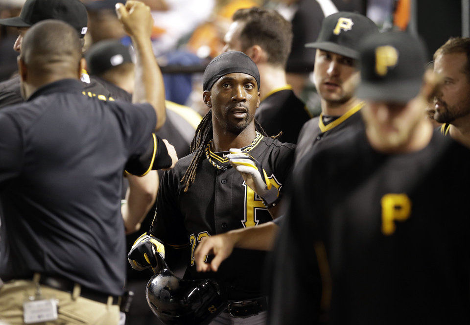 Photo - Pittsburgh Pirates' Andrew McCutchen, center, high-fives teammates in the dugout after scoring on a bases-loaded walk to Starling Marte in the first inning of the second baseball game of a doubleheader against the Baltimore Orioles, Thursday, May 1, 2014, in Baltimore. (AP Photo/Patrick Semansky)