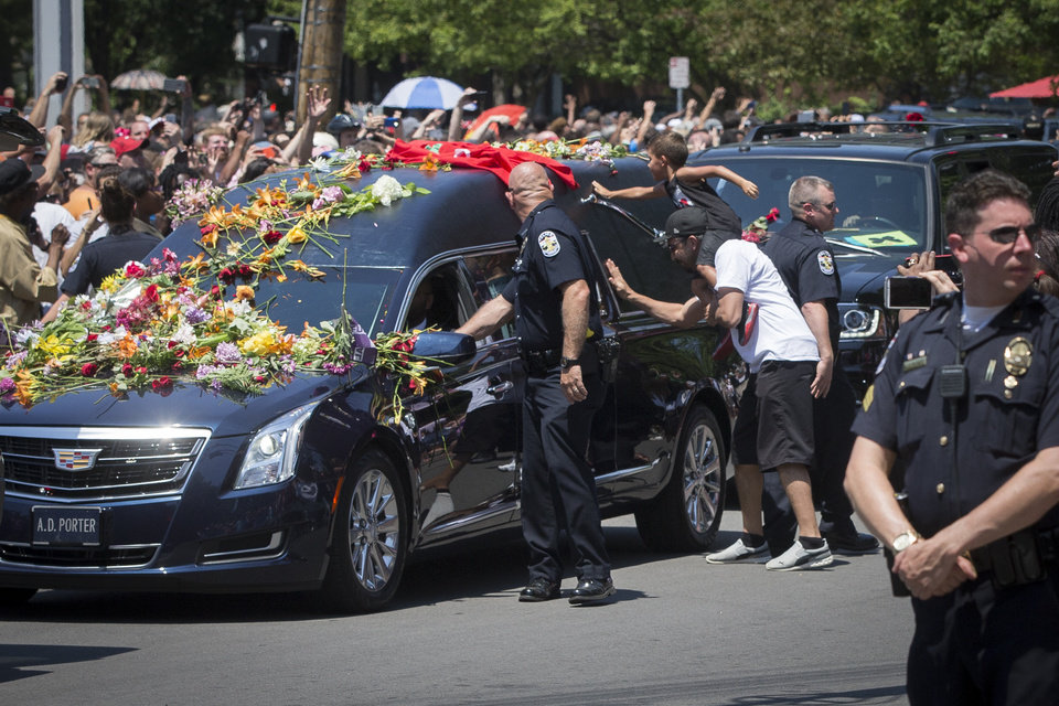 Photo - Spectators touch the hearse carrying Muhammad Ali as it arrives while crowds watch his funeral procession enter Cave Hill Cemetery, Friday, June 10, 2016, in Louisville, Ky.   (AP Photo/John Minchillo)