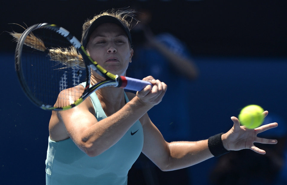 Photo - Eugenie Bouchard of Canada makes a forehand return to  Li Na of China during their semifinal at the Australian Open tennis championship in Melbourne, Australia, Thursday, Jan. 23, 2014.(AP Photo/Andrew Brownbill)