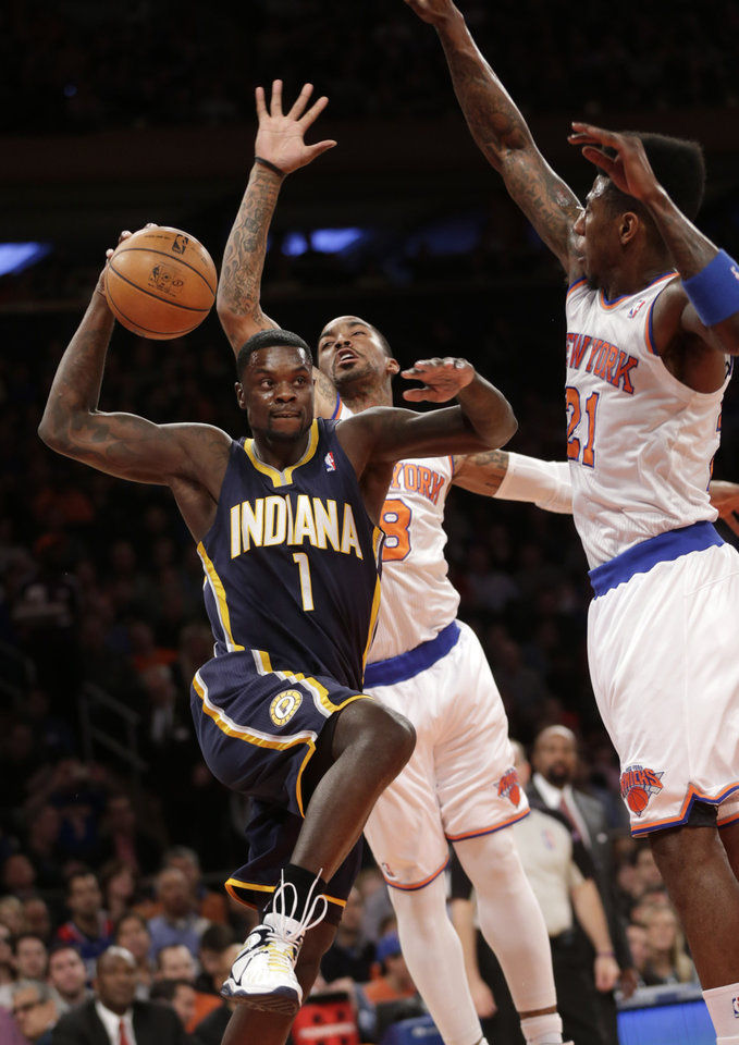 Photo - Indiana Pacers' Lance Stephenson, left, drives to the basket underneath New York Knicks' Iman Shumpert, right, and J.R. Smith during the first half of the NBA basketball game, Sunday, April 14, 2013, in New York. (AP Photo/Seth Wenig)
