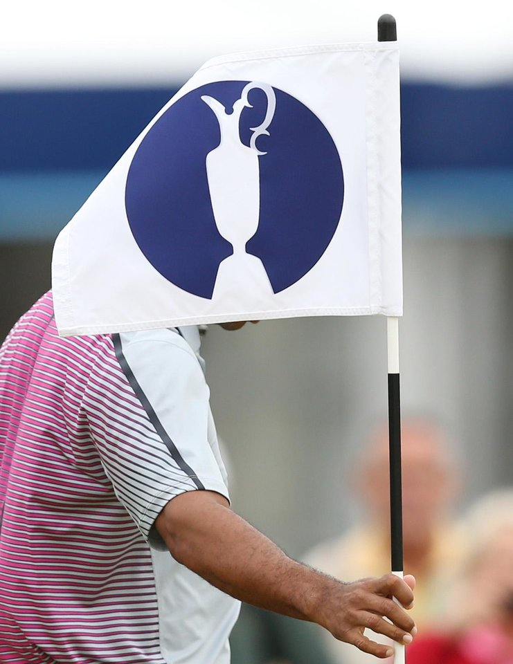 Photo - Tiger Woods of the US removes the flag from the hole on the practice green ahead of the British Open Golf championship at the Royal Liverpool golf club, Hoylake, England, Wednesday July 16, 2014. The British Open Golf championship starts Thursday July 17. (AP Photo/Scott Heppell)