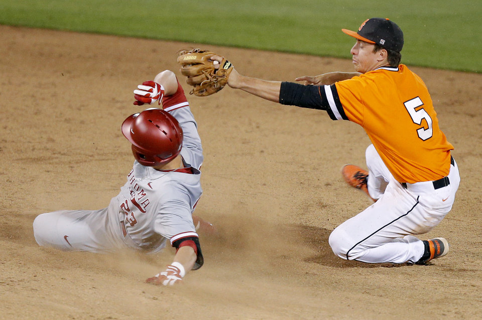 Photo - OSU's Donnie Walton falls back after tagging out OU's Kilbey Carpenter at second base in the 16th inning of a Bedlam baseball game between Oklahoma State University and the University of Oklahoma in Stillwater, Tuesday, April 15, 2014. Photo by Bryan Terry, The Oklahoman