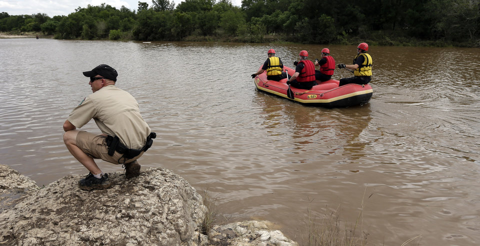 Members of a the Shertz Fire Department and Texas Parks and Wildlife search Sunday, May 26, 2013, in Shertz, Texas, for a missing teen who was swept away in a rain swollen Cibilo Creek Saturday. (AP Photo/Eric Gay)