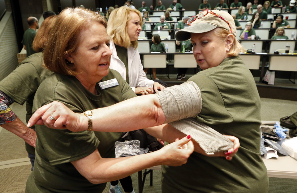 Photo -  Trudy Middleton applies an emergency bandage to Katie Reynolds during a Safety Day training exercise at Moore Norman Technology Center. Staff went through drills involving fire, trauma, suspected active shooters and/or bomb threats.   [Photo by Steve Sisney, The Oklahoman]