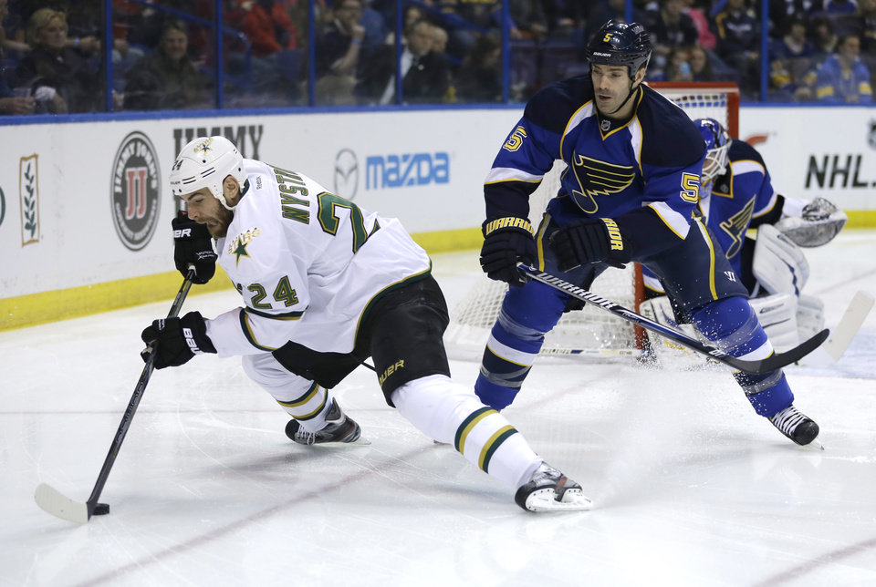 Photo - Dallas Stars' Eric Nystrom, left, reaches for a puck as St. Louis Blues' Barret Jackman watches during the first period of an NHL hockey game Friday, April 19, 2013, in St. Louis. (AP Photo/Jeff Roberson)