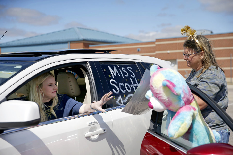 Photo - Michelle Flipski, a kindergarten teacher assistant hands kindergarten teacher Lindsey Scott poster baord to decorate before an Oakridge Elementary faculty caravan through neighborhoods around the Moore school, Tuesday, March 24, 2020. [Bryan Terry/The Oklahoman]