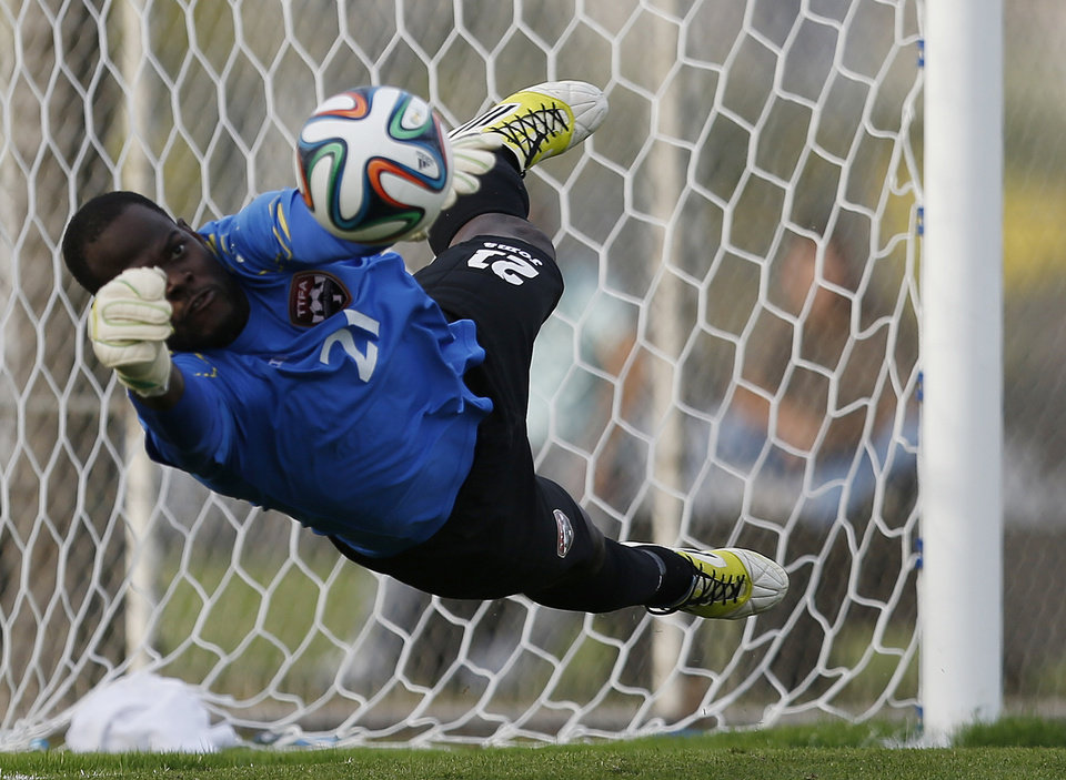 Photo - Trinidad and Tobago goalkeeper Jan Michael Williams makes a save on a penalty shot by Iran's Javad Nekounam during the second half of an international soccer friendly at the Corinthians soccer team training center Sao Paulo, Brazil, on Sunday, June 8, 2014. Iran will play in group F of the 2014 soccer World Cup. (AP Photo/Julio Cortez)