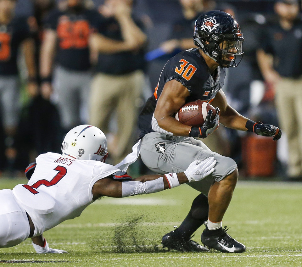 Photo - Oklahoma State's Chuba Hubbard (30) carries the ball as South Alabama's Tobias Moss (2) defends in the first quarter during a college football game between Oklahoma State (OSU) and South Alabama at Boone Pickens Stadium in Stillwater, Okla., Saturday, Sept. 8, 2018. Photo by Nate Billings, The Oklahoman