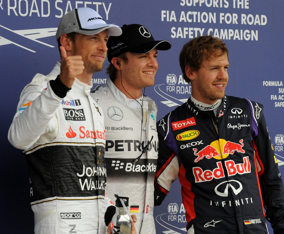 Photo - Germany's Nico Rosberg of Mercedes, centre, who won the pole position,  Germany's Sebastian Vettel, right, of Red Bull, who finished second, and Britain's Jenson Button, left, of McLaren Mercedes who finished third, pose for the photographers following the qualifying session of the British Formula One Grand Prix at Silverstone circuit, Silverstone, England, Saturday, July 5, 2014. The British Formula One Grand Prix will be held on Sunday, July 6, 2014. (AP Photo/Rui Vieira)
