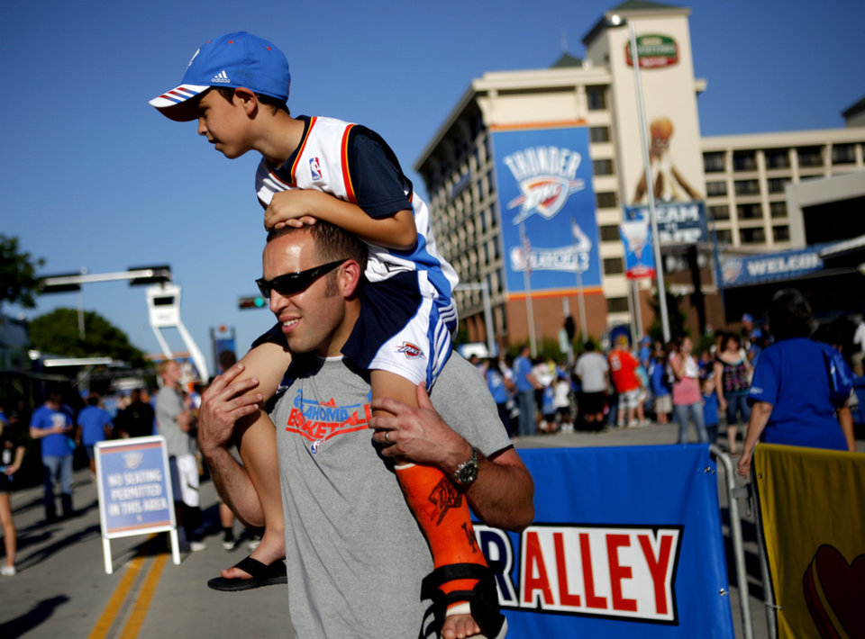 Photo - Dustin Judd carries his son Dyson Judd, 7, of Edmond outside the arena before Game 5 in the second round of the NBA playoffs between the Oklahoma City Thunder and the L.A. Lakers at Chesapeake Energy Arena in Oklahoma City, Monday, May 21, 2012. Photo by Bryan Terry, The Oklahoman