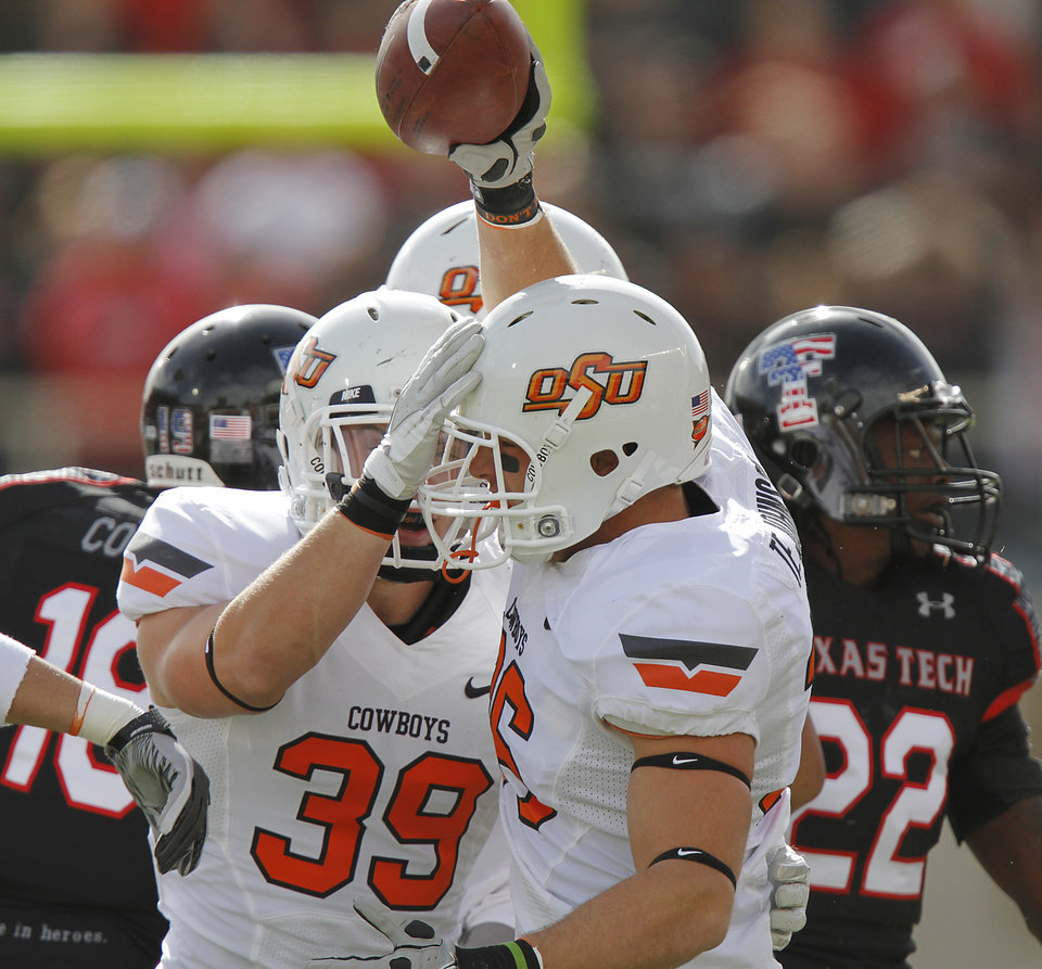 Photo - Oklahoma State Cowboys linebacker Teddy Johnson (36) celebrates a fumble recovery with Kyle Hale (39) during the college football game between the Oklahoma State University Cowboys (OSU) and Texas Tech University Red Raiders (TTU) at Jones AT&T Stadium on Saturday, Nov. 12, 2011. in Lubbock, Texas.  Photo by Chris Landsberger, The Oklahoman