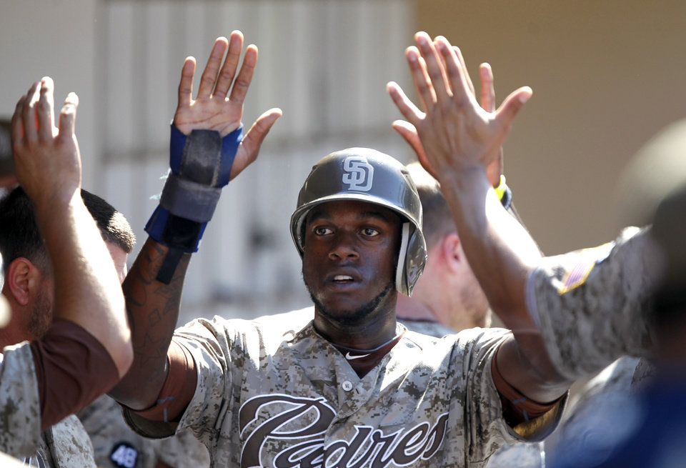 Photo -   San Diego Padres' Cameron Maybin is congratulated in the dugout after scoring against the Colorado Rockies during the fifth inning of their baseball game in San Diego, Sunday, Sept. 16, 2012. (AP Photo/Alex Gallardo)