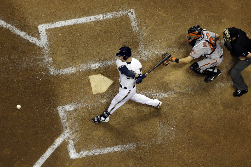 Photo - Milwaukee Brewers' Jonathan Lucroy hits an RBI single during the ninth inning of a baseball game against the Baltimore Orioles Tuesday, May 27, 2014, in Milwaukee. (AP Photo/Morry Gash)