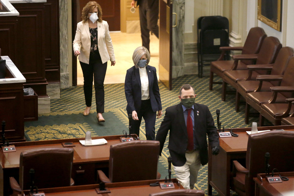 Photo - Representatives enter the House chamber to vote during a special session of the House of Representatives at the state Capitol in Oklahoma City, Monday, April 6, 2020. A skeleton crew of lawmakers was allowed in the House chamber as others watched from their offices during a special session of the House of Representatives. [Bryan Terry/The Oklahoman]