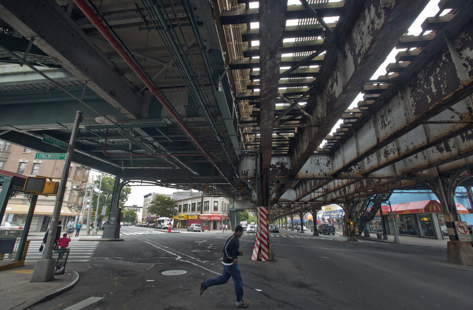 Photo - A young man runs under an elevated section of subway tracks in The Bronx borough of New York,  Wednesday, May 22, 2013.  A company that offered tourist treks to the Bronx