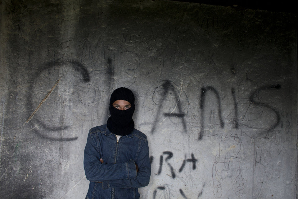 Photo - AP10ThingsToSee - A young Honduran migrant, who hoped to find work in the U.S., wears a balaclava provided by a volunteer group aiding migrants, as he shields himself from cold and rain, while waiting for a northbound train beside a garbage dump in Huehuetoca, outside Mexico City, Wednesday, July 30, 2014. (AP Photo/Rebecca Blackwell)