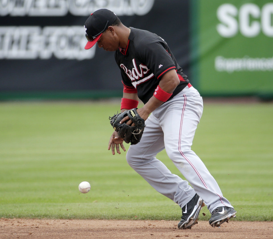 Photo - Cincinnati Reds shortstop Ramon Santiago fields a ball hit by San Francisco Giants catcher Buster Posey during the second inning of a spring training baseball game in Scottsdale, Ariz., Thursday, March 6, 2014. (AP Photo/Chris Carlson)