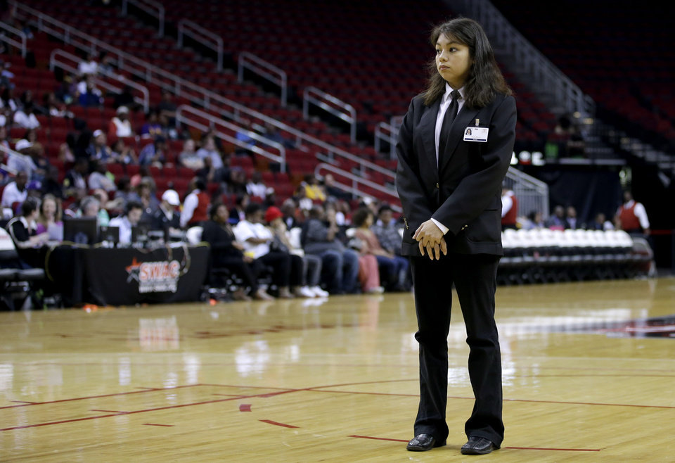 Photo - In this photo taken on March 15, 2014, Toyota Center security guard Sandra Rivera stands on the court while keeping an eye on fans during a timeout in the first half of an NCAA college basketball game between Texas Southern and Prairie View A&M in the championship of the Southwestern Athletic Conference tournament in Houston. Security firms charged with protecting college and professional sports venues are monitoring social media more than ever to prepare for everything from a garden-variety court storming to something much more dangerous.  (AP Photo/David J. Phillip)