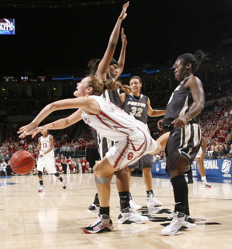 Photo - OU's Whitney Hand gets tripped up between Purdue's Alex Guyton, left, Lindsay Wisdom-Hylton, and FahKara Malone during the NCAA women's basketball regional  tournament finals between Oklahoma and Purdue at the Ford Center in Oklahoma City, Tuesday, March 31, 2009.  Photo by Bryan Terry, The Oklahoman