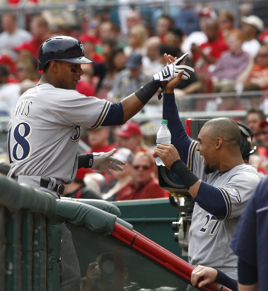 Photo - Milwaukee Brewers' Khris Davis (18) is congratulated by Carlos Gomez (27) after Davis hit a solo home run off Cincinnati Reds starting pitcher Alfredo Simon (31) during the fourthinning of a baseball game, Sunday, May 4, 2014, in Cincinnati. (AP Photo/David Kohl)