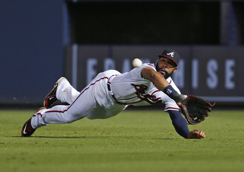 Photo - Atlanta Braves right fielder Jason Heyward makes a diving catch for the out on Philadelphia Phillies' Ryan Howard in the eighth inning of a baseball game in Atlanta, Friday, July 18, 2014.(AP Photo/John Bazemore)