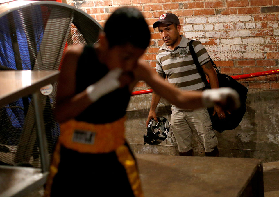 Photo -  Felipe Barba watches his son, Chris Barba, 9, of Edmond, warm up before his first fight at The Underground Arena in Oklahoma City, Saturday, June 15, 2013. Photo by Bryan Terry, The Oklahoman