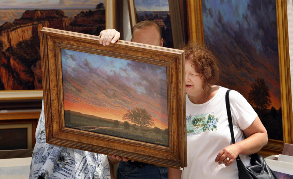 Photo - Donna J. Reynolds thoroughly examines a painting by Edmond artist Rory Morgan during May Fair Arts Festival in Norman, Okla. on Friday, May 1, 2009.   Photo by Steve Sisney, The Oklahoman