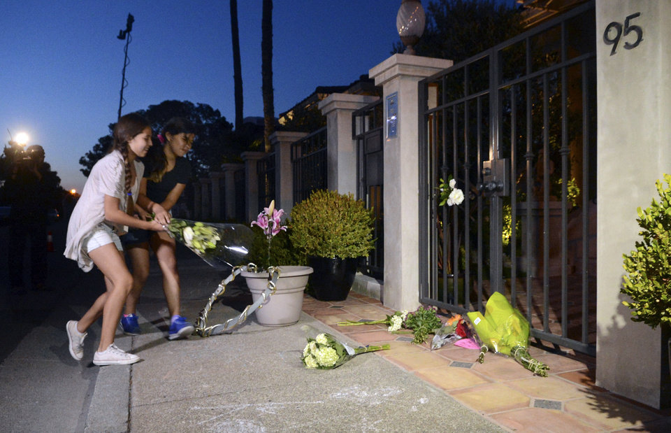 Photo - In this photo taken on Monday, Aug. 11, 2014, Isabel Martinez, 12, left, and Natasha Guadalupe, 11, both of Novato, Calif., place flowers on the sidewalk in front of the home of actor Robin Williams in Tiburon, Calif. Williams died Monday in an apparent suicide at his San Francisco Bay Area home, according to the sheriff's office in Marin County, north of San Francisco. (AP Photo/Marin Independent Journal, Alan Dep)