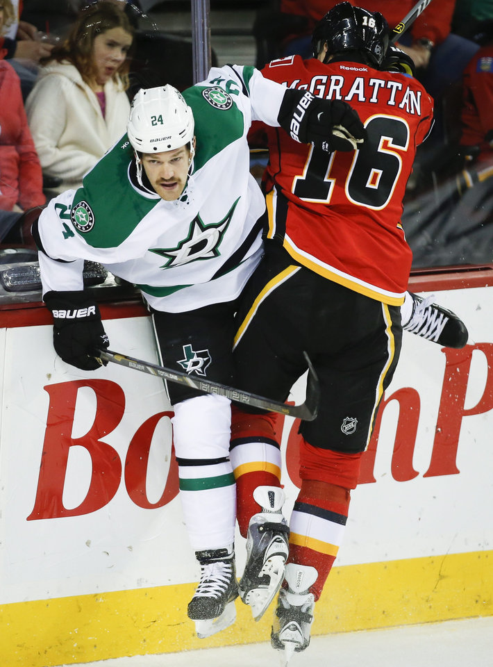Dallas Stars' Jordie Benn, left, is checked by Calgary Flames' Brian McGrattan during first-period NHL hockey game action in Calgary, Alberta., Thursday, Nov. 14, 2013. (AP Photo/The Canadian Press, Jeff McIntosh)