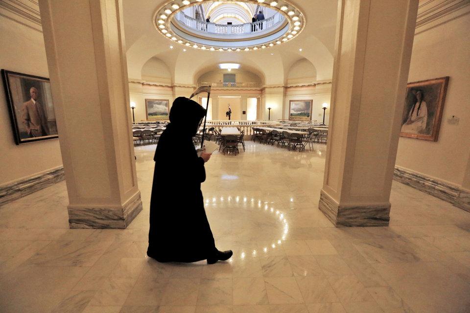 "The ""Grim Reaper"" walks Tuesday in the rotunda of the state Capitol as part of Gov. Mary Fallin's announcement for plans to put tobacco regulations aimed at reducing secondhand smoke to a vote of the people. Photo By Steve Gooch, The Oklahoman"