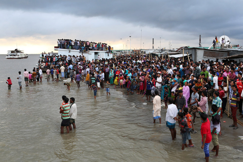Photo - People gather on the banks of  the River Padma after a passenger ferry capsized in Munshiganj district, Bangladesh, Monday, Aug. 4, 2014. A passenger ferry carrying hundreds of people capsized Monday in central Bangladesh, and at least 44 people either swam to safety or were rescued but the number of missing passengers is not yet known. (AP Photo/ A.M. Ahad)