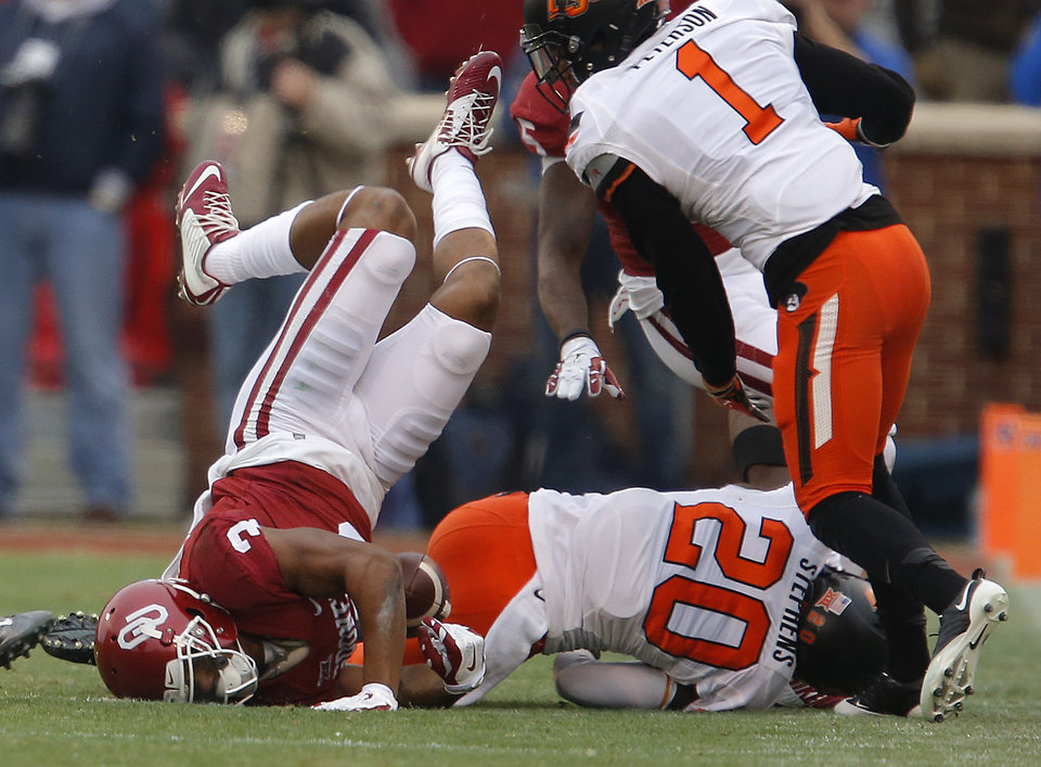 Photo - Oklahoma's Sterling Shepard (3) hits the ground beside Oklahoma State's Larry Stephens (20) and Oklahoma State's Kevin Peterson (1)  during a Bedlam college football game between the University of Oklahoma Sooners (OU) and the Oklahoma State Cowboys (OSU) at Gaylord Family-Oklahoma Memorial Stadium in Norman, Okla., Saturday, Dec. 6, 2014. Photo by Bryan Terry, The Oklahoman