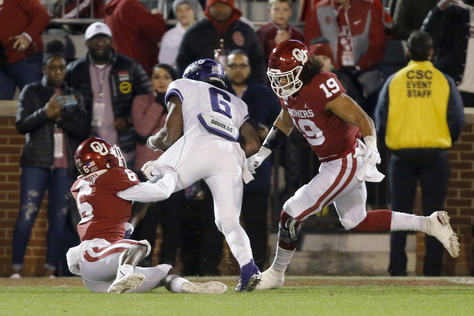 Photo - Oklahoma's Caleb Kelly (19) and Tre Brown (6) bring down TCU's Darius Anderson (6) during an NCAA football game between the University of Oklahoma Sooners (OU) and the TCU Horned Frogs at Gaylord Family-Oklahoma Memorial Stadium in Norman, Okla., Saturday, Nov. 23, 2019. Oklahoma won 28-24. [Bryan Terry/The Oklahoman]