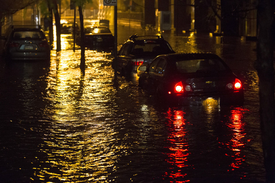 Vehicles are submerged during a storm surge near the Brooklyn Battery Tunnel, Monday, Oct. 29, 2012, in New York. Superstorm Sandy zeroed in on New York's waterfront with fierce rain and winds that shuttered most of the nation's largest city Monday, darkened the financial district and left a huge crane hanging off a luxury high-rise. (AP Photo/ John Minchillo) ORG XMIT: NYJM122