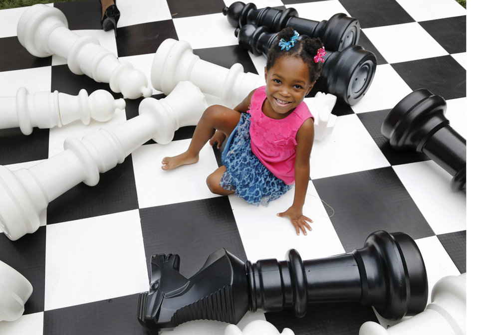 "Photo - ""Miracle"" child Jalesa plays on an oversized chess board at a Mariane's Rentals for Special Events music video shoot. Former patients, Miss Oklahoma and other pageant queens helped produce a video to benefit Children's Miracle Network Hospitals.  Photo by Jim Beckel,  The Oklahoman  Jim Beckel - THE OKLAHOMAN"