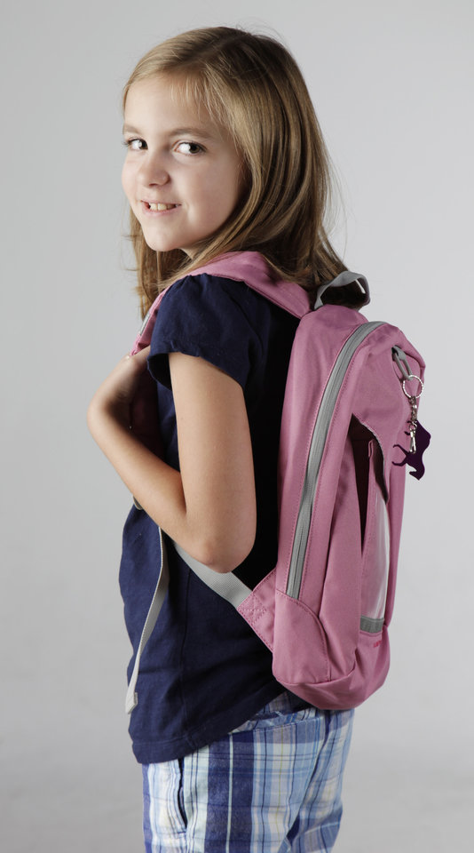 Photo - CHILDREN / KIDS: Claire Argo, 8, models a backpack in the OPUBCO studio Thursday, July 23, 2009. Photo by Doug Hoke, The Oklahoman. ORG XMIT: KOD